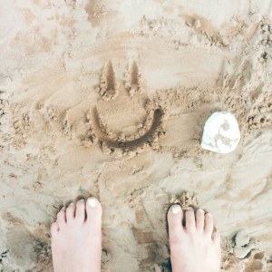 Toes in sand with a happy face drawn in it.