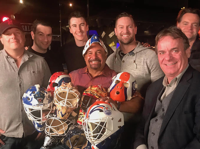 Team wrap photo with NHL legend Grant Fuhr holding most of his old NHL masks