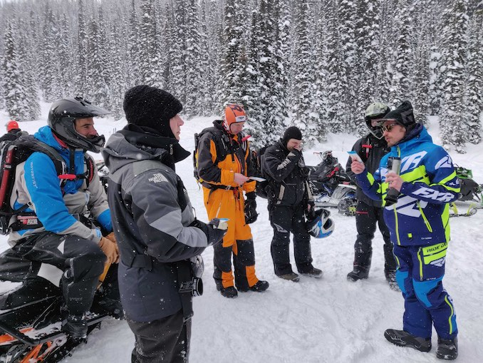 Grant Helgeson interacts with backcountry snowmobilers at Quartz Creek, near Golden, BC.
