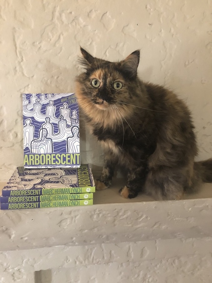 (Photo by Michaela Stephen) Banana Loaf posing next to my debut novel, Arborescent (Arsenal Pulp Press 2020).