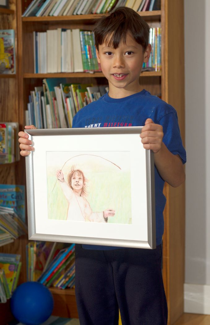 Phillip. Luka holding a portrait done when he was just a toddler.