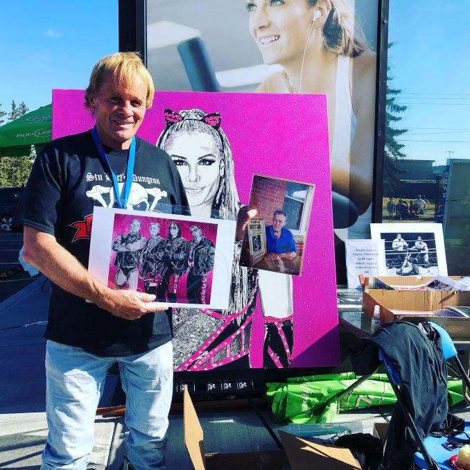 Former professional wrestler, Bruce Hart, holding Kim's oil paintings.