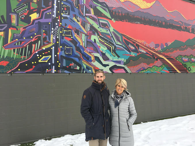 my son Justin in front of a mural I created for the North Glenmore Park Community Association.